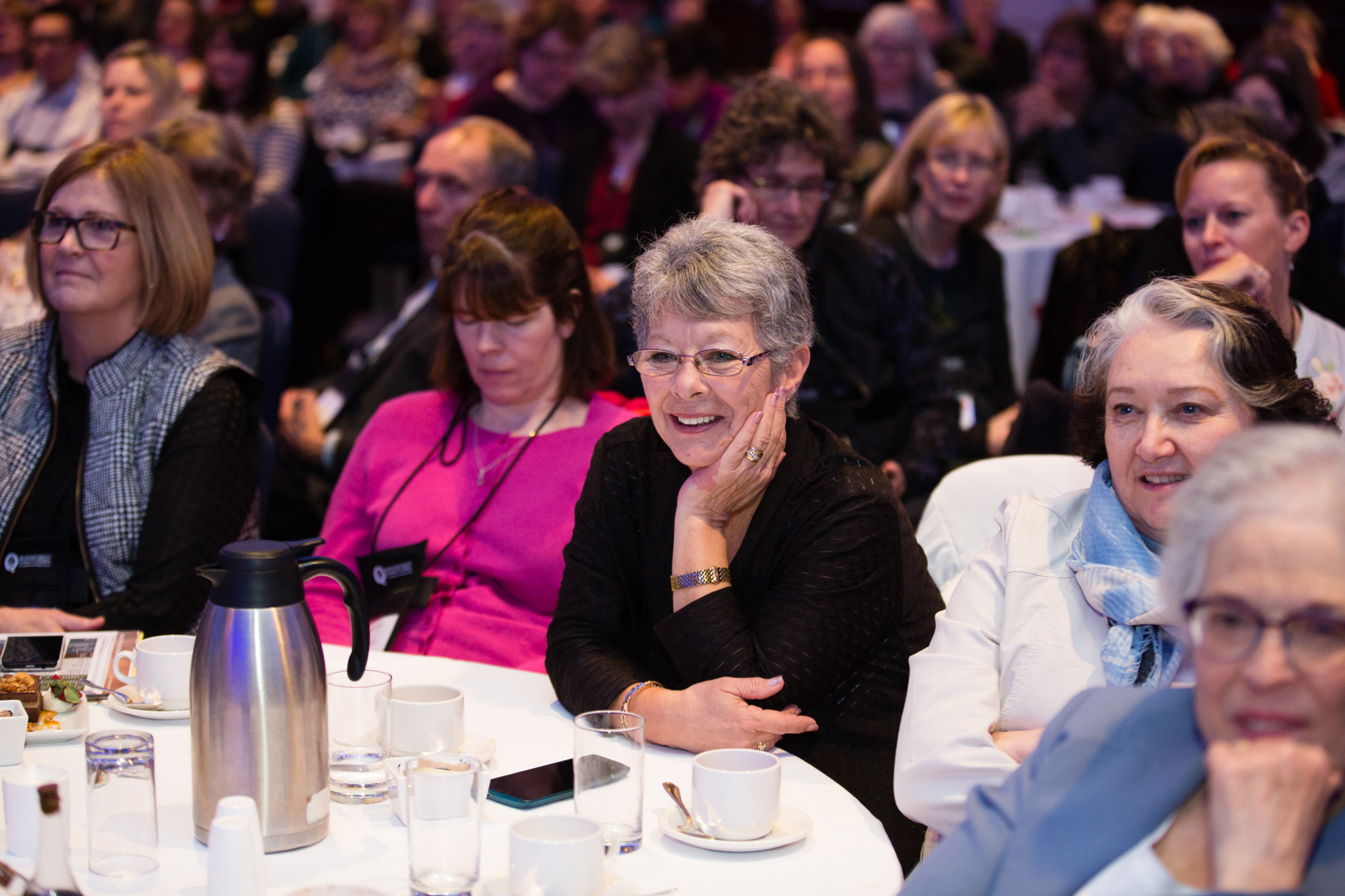 A woman smiles while listening to a speech at the BC Quality Forum