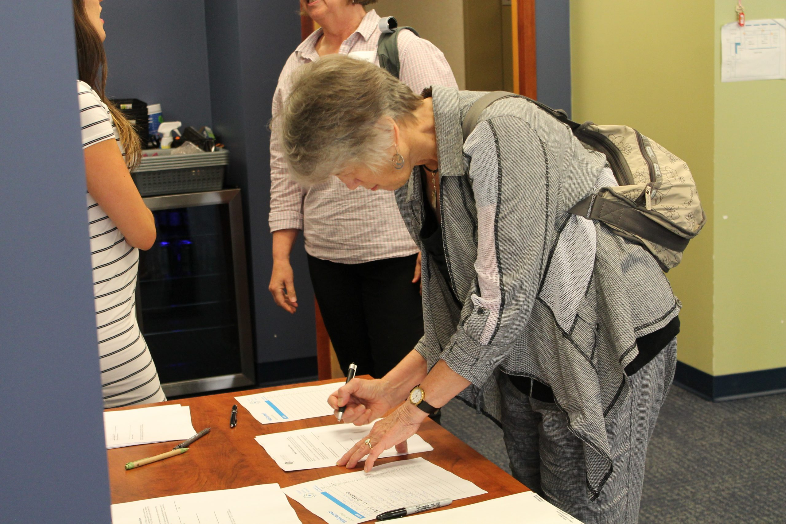 A woman writes on a piece of paper at the coffee networking event in Vancouver