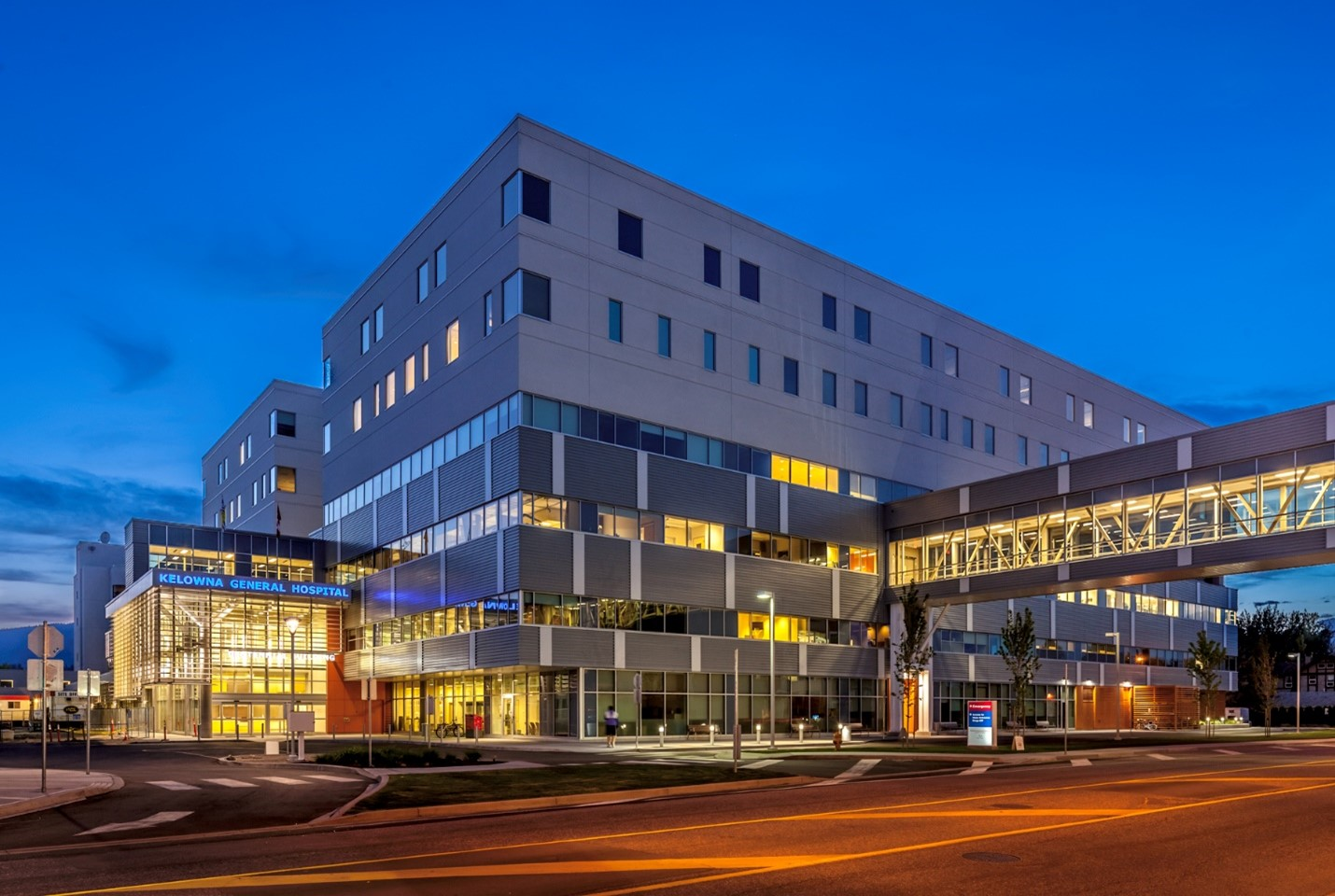 A photo of Kelowna General Hospital at dusk, with a dark blue sky.