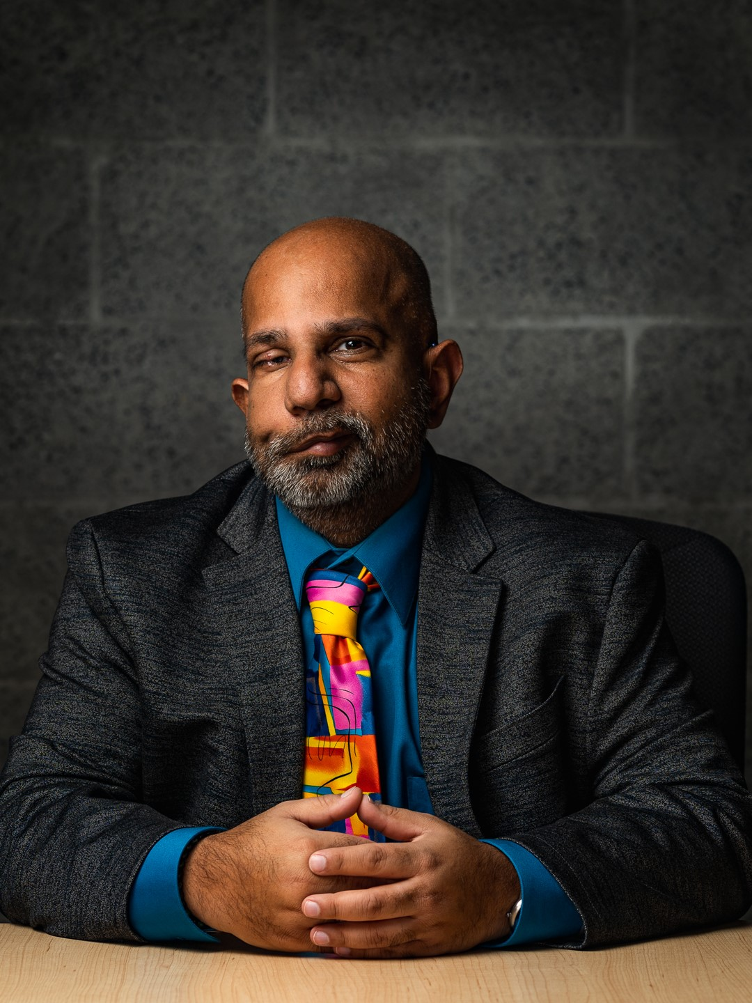Vikram is wearing a suit with a colourful tie and looking into the camera.